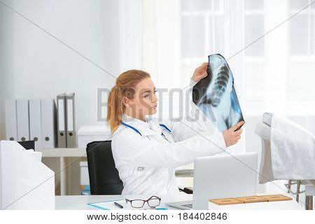 Beautiful young orthopedist working in office