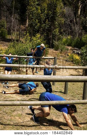 People passing through hurdles during obstacle course in boot camp