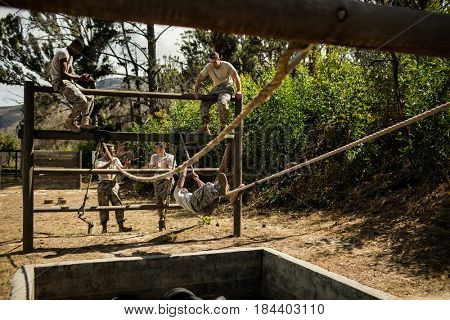 Young military soldiers practising rope climbing during obstacle course at bootcamp