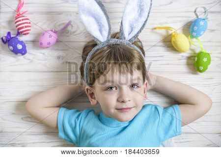 Easter concept. Happy cute child wearing bunny ears lay on wooden background dreaming about holiday