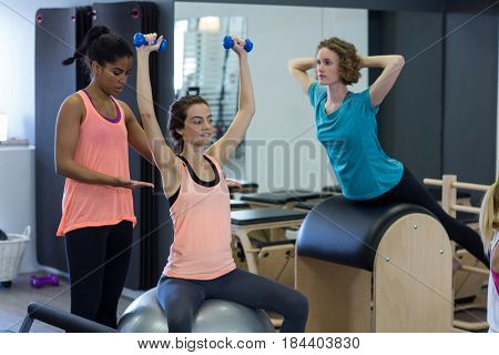 Female trainer assisting woman with stretching exercise on fitness ball in gym