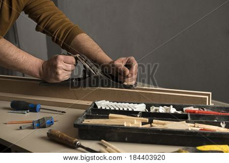 Carpenter planing a plank of wood with a hand plane close up.