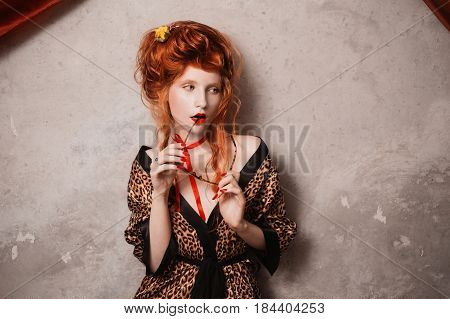A glamour woman with red hair in leopard glamour print gown with glasses in hand. Red-haired glamour girl with pale skin and blue eyes with a bright unusual appearance with a red ribbon around her neck. French glamour courtesan