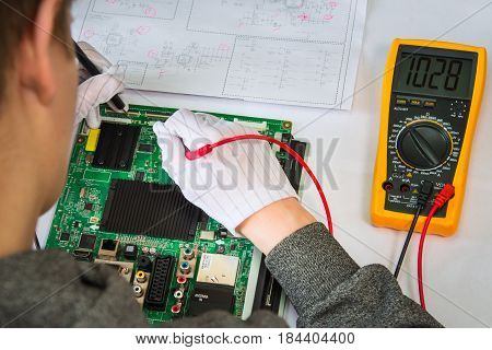 Computer repair service, hands of man tech testing motherboard with tools.