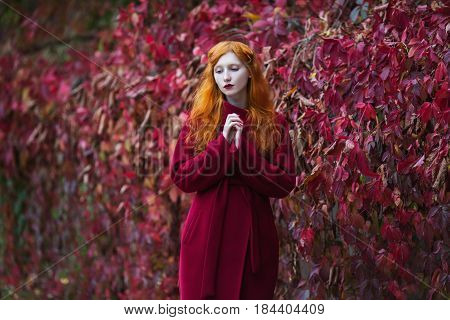 Woman with red straight hair in a red coat on a bright autumn background. Red-haired girl with pale skin and blue eyes and a bright unusual appearance with a ring on finger and red nails. Street style