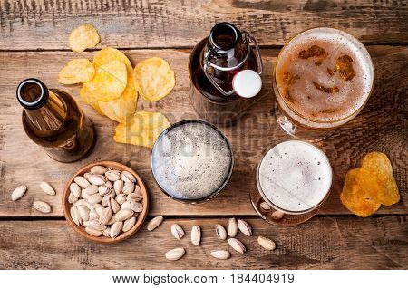 Beer in bottles and glasses on a wooden table. Beer and snacks are pistachio nuts chips and nachos top view. Drink and snack for the football match or rest in pub
