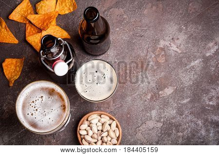 Beer in bottles and glasses on the concrete table. Beer and snacks are pistachio nuts chips and nachos top view. Copy space. Drink and snack for the football match or rest in pub