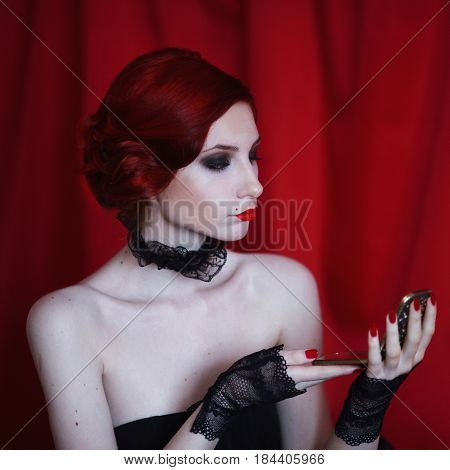 Woman with red curly hair in a black dress and retro makeup looks in the mirror on red background. Red-haired girl with pale skin blue eyes unusual appearance red lips and a fatal face. Noir woman