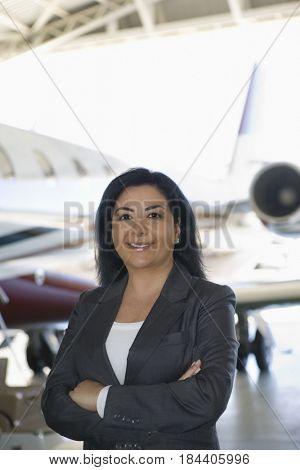 Hispanic businesswoman standing in airplane hangar