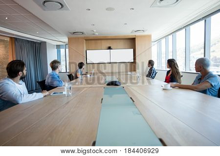 Creative business team attending a video call in conference room at office