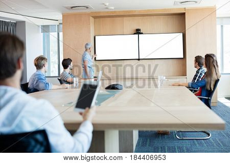 Rear view of man holding a tablet while attending a meeting in conference room