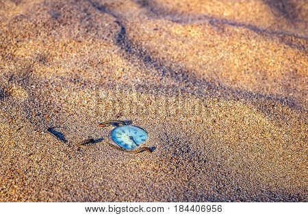Antique rotten pocket watch buried partial in the golden sand.