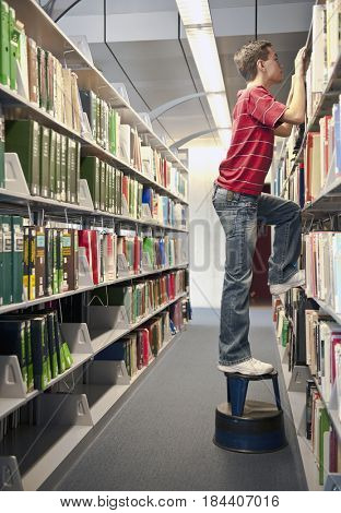 Hispanic student on footstool peering over library shelves