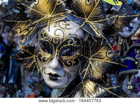 Handcrafted venetian mask suspended on outdoor vendor stands