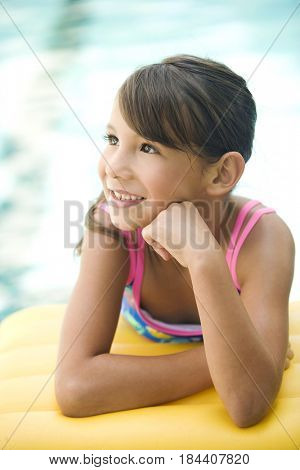 Smiling mixed race girl leaning on pool raft