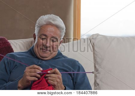 Hispanic man sitting on sofa knitting