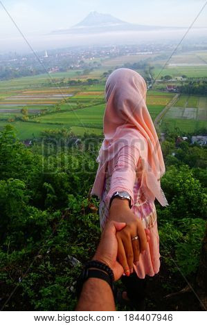 A moslem tourist looking for merapi mountain view in Yogyakarta, Indonesia