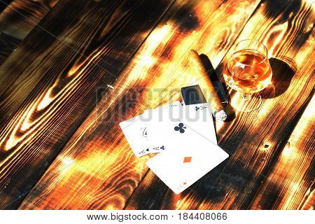 Glass with alcohol cigarettes and playing cards on a wooden table