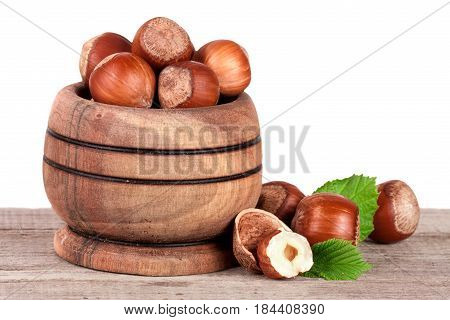 Hazelnuts with leaves in a wooden bowl on a wooden table with a white background.