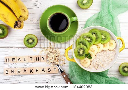 Breakfast with oatmeal porridge coffee cup and fruits. Oatmeal with kiwi and banana. Healthy breakfast concept. Top view