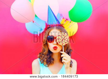 Portrait Woman In A Birthday Cap Is Blowing Lips Is Closes Her Eye With A Lollipop On Stick Over An