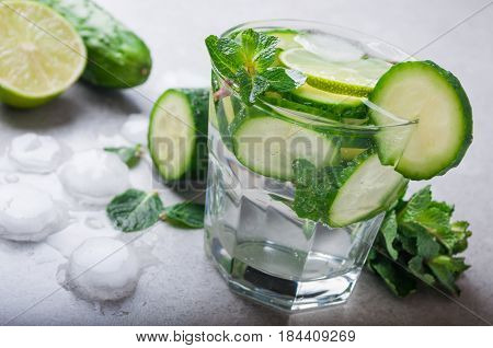 Cold and refreshing water with cucumber and mint on grey background. Summer drink cucumber lemonade. Healthy drink and detox concept