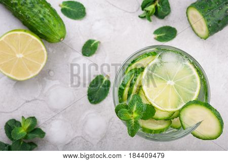 Refreshing water with cucumber mint and lime on grey background top view. Summer drink cucumber lemonade. Healthy drink and detox concept