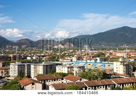 PISA ITALY - August 2 2015: Village of Pisa in Tuscany Italy showing rooftops Garibaldi Football Stadium and distant mountains. Pisa is a popular Italian tourist destination.