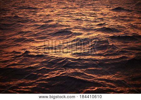 Sea surface background in sunset or sunrise time and feeling alone. wave of water or sea flowing with turbulent in the nature. nature concept with sea surface background and many bubble in the water.