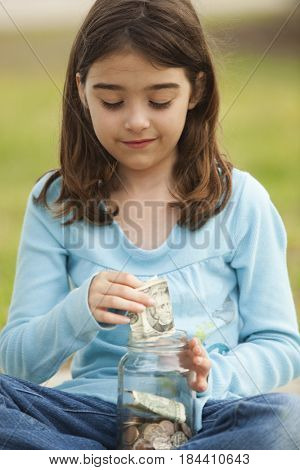 Caucasian girl taking money from jar