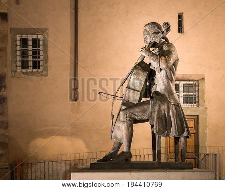 LUCCA ITALY - August 4 2015: Statue of Luigi Boccherini a famous Italian classical era composer and cellist from the Tuscan village of Lucca Italy. Seated and playing his cello outside of the famous city Music Academy.