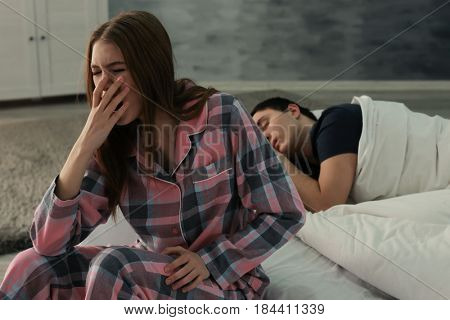 Young woman with sleep disorder sitting on bed at home