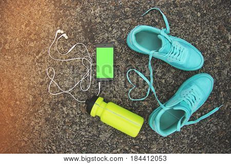 Sports equipment and love concept. Portrait of blue sports shoes with shoelaces shaped in form of heart bottle of water and phone with green screen. Chromakey.