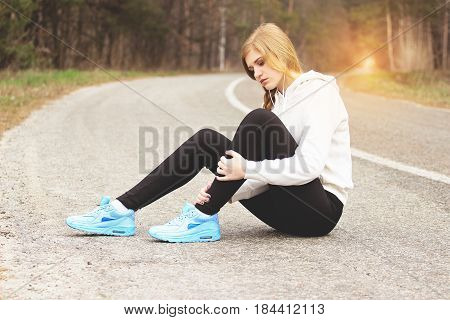 Ouch, It Hurts. Young And Beautiful Redhaired Sports Girl Hurt Her Leg And Sitting On The Road. Work