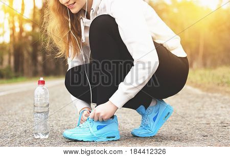 Running Athlete Girl. Portrait Of Young Sports Girl Tying Shoelaces On The Road. Healthy Lifestyle A