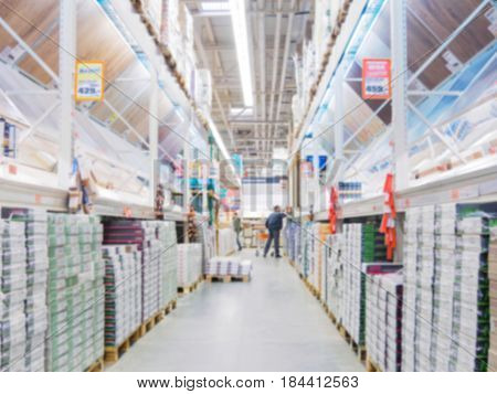Abstract blurred hardware store aisle with finishing material shelves and unrecognizable customers as background
