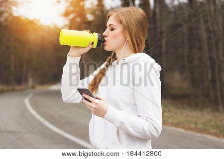 Good Water Balance. Portrait Of Thirsty Young Redhaired Sports Girl Drinking Water While Using Her P