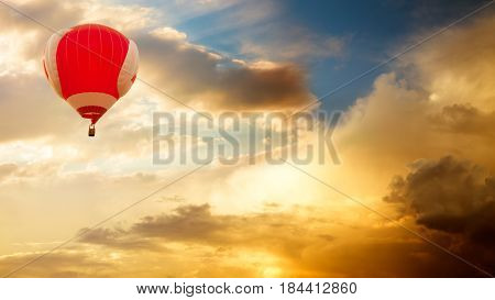Red Hot Air Balloon Flying over Golden Sunset Sky. Amazing Evening Clouds Background. Toned Photo with Copy Space. Travel, Adventure and Freedom Concept.
