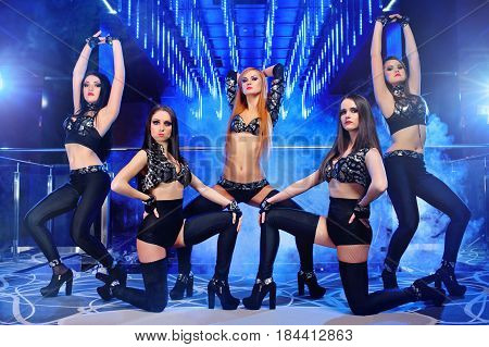 Full length shot of sexy female dancers group wearing matching black outfits posing at the night club athletes body figure women sexuality exotic femininity seductive show entertainment concept.