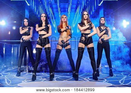 Group of sexy young female dancers performing at the night club wearing provocative black outfits dancing sensually entertainment leisure lighting artistic performance show go-go girls.