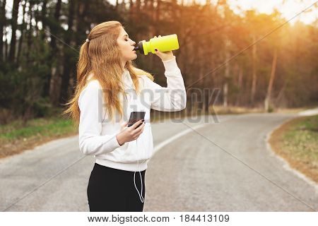 Time For Rest. Portrait Of Thirsty Young Redhaired Girl Drinking Water While Listening The Music On