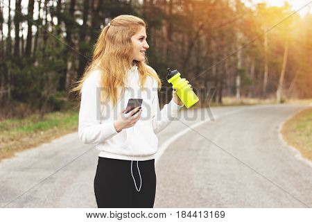 Enjoy The Jogging. Portrait Of Young And Pretty Redhaired Sports Girl Using The Phone While Having A