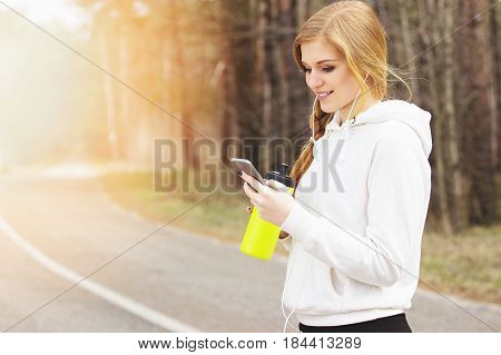 Sports Gadgets. Portrait Of Cheerful, Attractive Redhaired Sports Girl Using Her Phone While Listeni