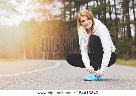 Have A Brake. Beautiful And Young Redhaired Sports Girl Tying Shoelaces On The Park Road. Morning Fi