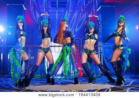 Shot of five sexy professional dancers wearing matching carnival outfits and masks performing at the nightclub disco dancing performance entertainment costume erotic exotic showgirls concept.