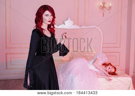 Two charming girls with red hair in retro charming dress in the bedroom. Femme fatale in a black charming dress and nice girl in white wedding charming dress. Fairy and Witch. Charming model posing in studio. Historical renaissance dresses.