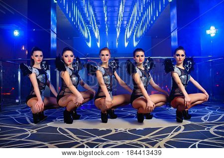Horizontal shot of five beautiful exotic dancers in similar outfits performing together at the disco club profession occupation job dancing performing entertaining leisure luxury enjoyment.