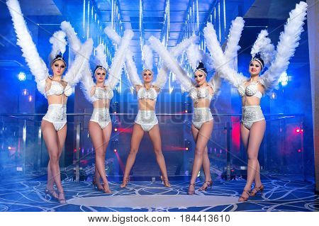 Full length shot of five gorgeous women dancing wearing white carnival outfits nightclub festival festive disco dance performance showgirls show time entertainment leisure enjoyment happiness.