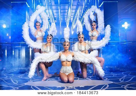 Five beautiful go-go dancers dressed in similar white carnival costumes with feather wings on their arms performing together on stage of a nightclub with artistic blue lighting entertainment dance.