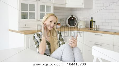 Wonderful young blonde in checkered shirt smiling and taking self portrait while sitting on chair in kitchen.